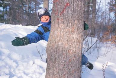 boy behind tree
