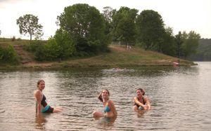 three girls swimming in a lake
